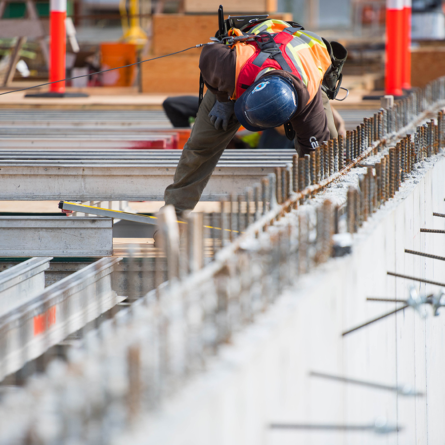 construction worker measuring steel roof